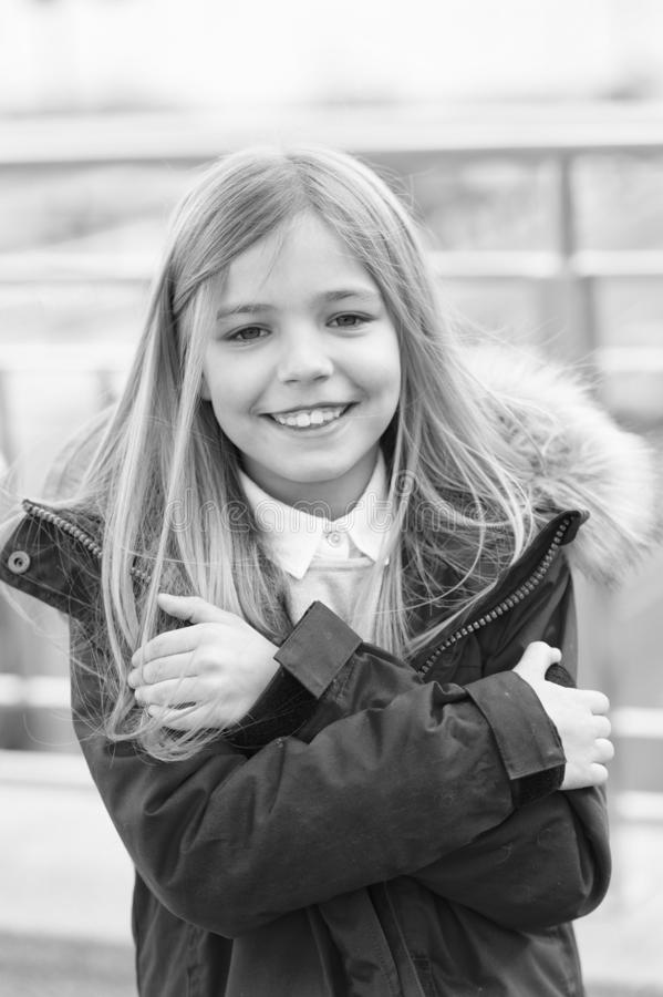 Kid smiling girl wear coat jacket with fur on hood but feels cold. Cold weather concept. She is freezing. Baby hug. Herself because of cold weather. Kid try to royalty free stock photos