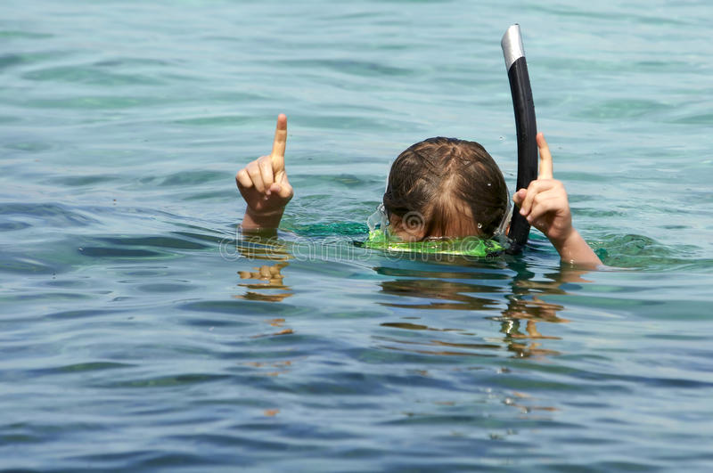 Kid snorkelling. Showing size of fish stock photo