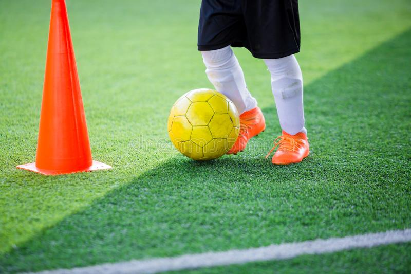 Kid soccer player control ball around cone maker for soccer training. On green artificial turf royalty free stock photography