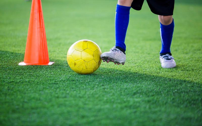 Kid soccer player control ball around cone maker for soccer training. On green artificial turf stock image