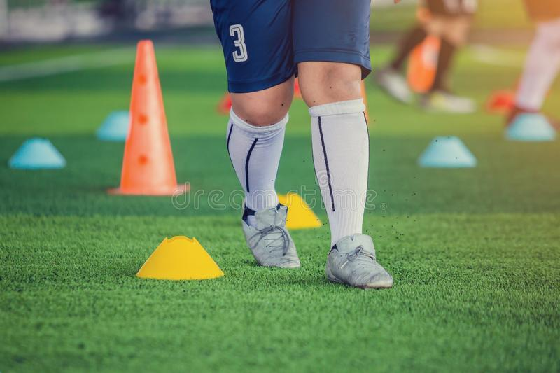 Kid soccer player Jogging and jump between cone markers. On green artificial turf for soccer training. Football or Soccer Academy stock image