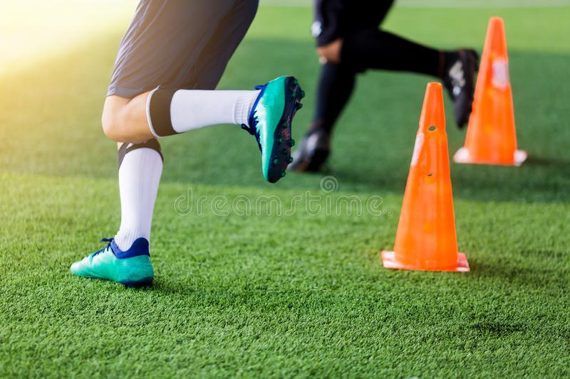 Kid soccer players are Jogging and jumping between cone marker. Kid soccer players are Jogging and jumping between cone marker for football training stock images