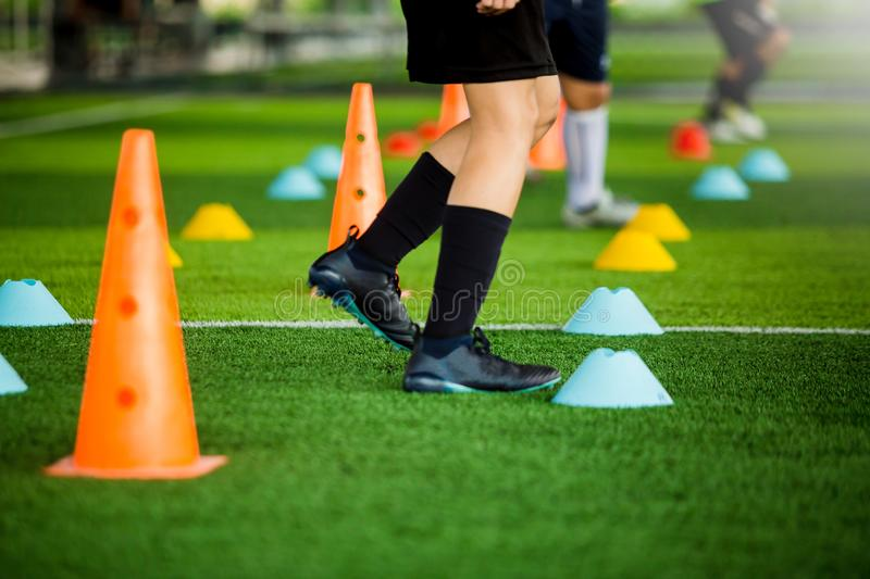 Kid soccer team jogging between yellow and blue marker cones for football training on green artificial turf. It is activity on holiday in soccer academy royalty free stock photos