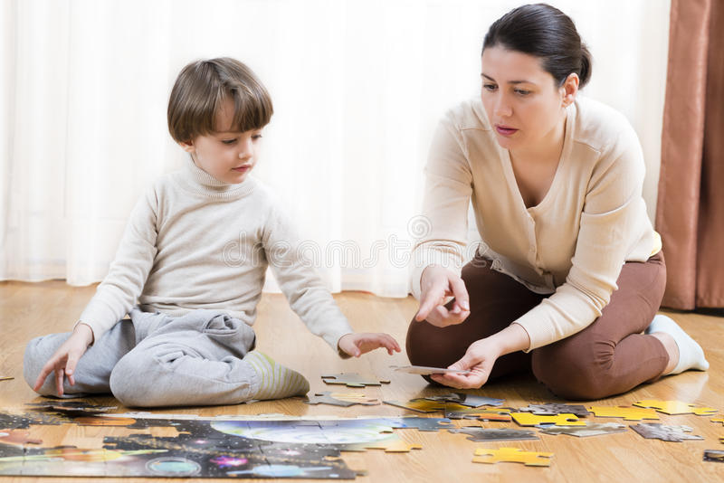 Kid Solving a Puzzle. Kid solving a floor puzzle at home being helped by his mother royalty free stock image