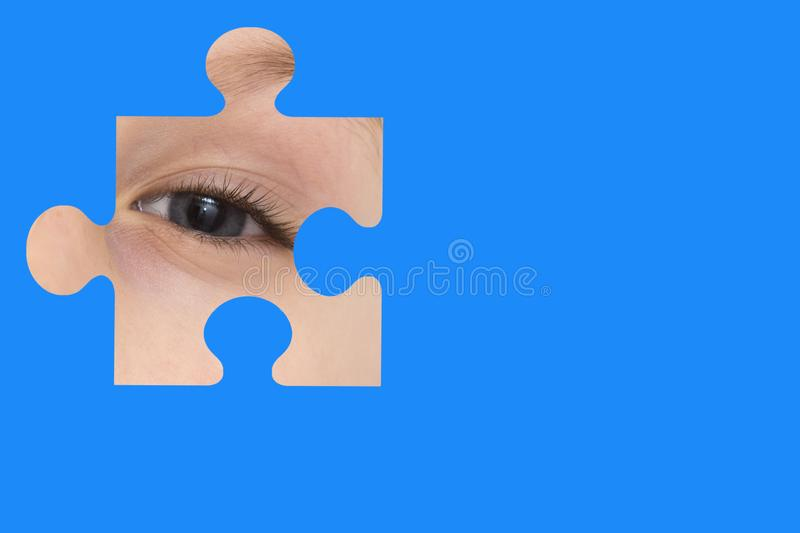 Kid spies through a blue puzzle. Symbol of autism awareness.  royalty free stock images