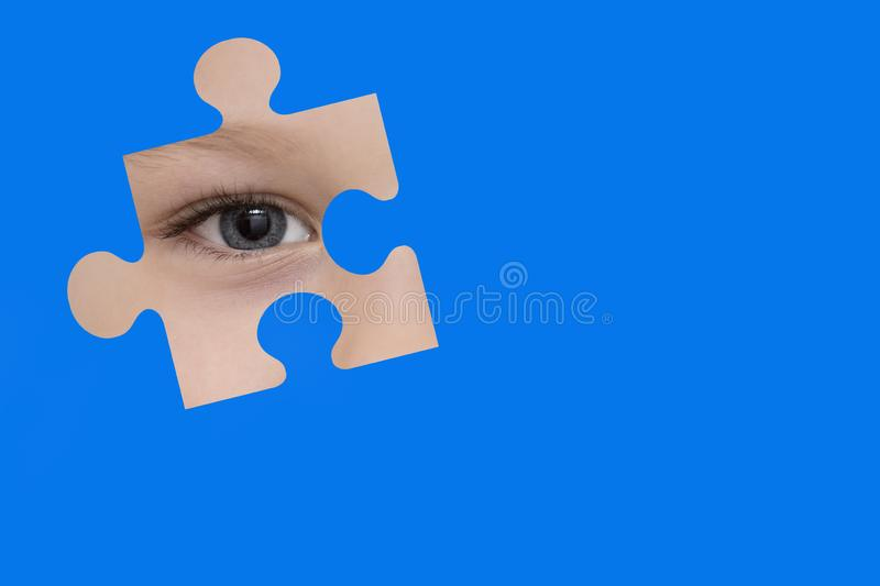 Kid spies through a blue puzzle. Symbol of autism awareness.  royalty free stock photo