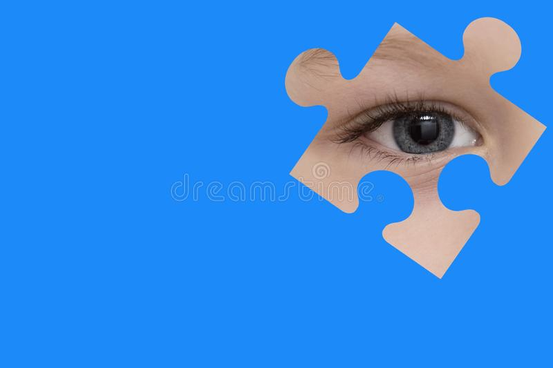 Kid spies through a blue puzzle. Symbol of autism awareness.  royalty free stock image