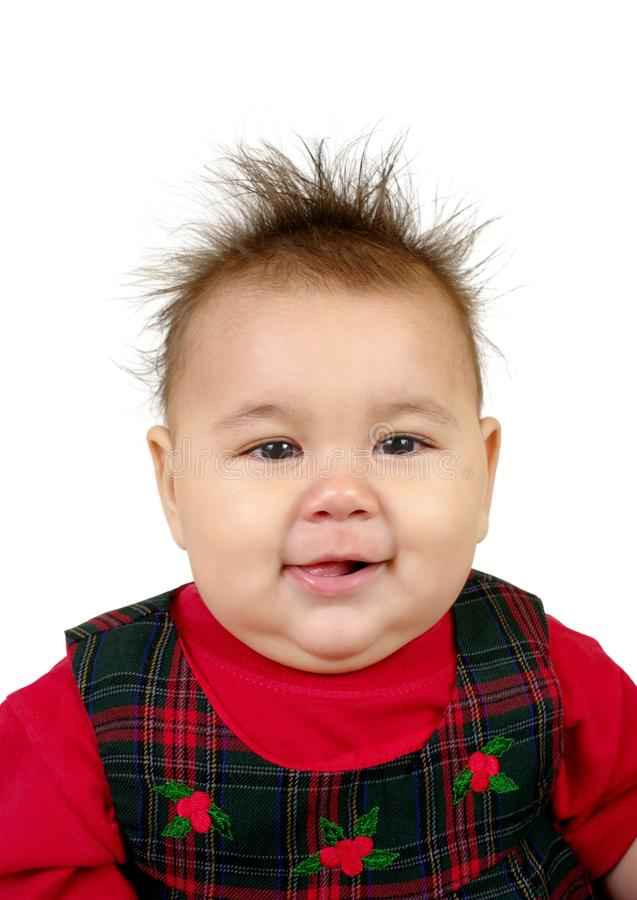 Kid with spiky hair. Cute nine-month-old baby girl with funny spiky hair, wearing a red holiday-type outfit, isolated on white background stock images