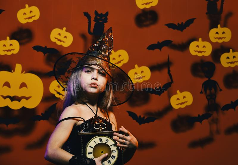 Kid in spooky witches costume holds old clock. Halloween party and decorations concept. Little witch wearing black hat royalty free stock photos