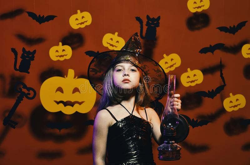 Kid in spooky witches costume holds old gas lamp.Haloween party and decorations concept. Little witch wearing black hat. Kid in spooky witches costume holds old royalty free stock photography