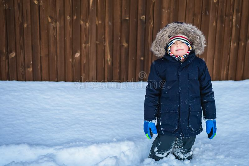 Kid standing in a deep snow stock image