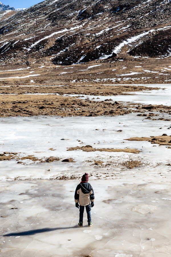 Kid stands on the frozen pond in winter at Zero Point at Lachung. North Sikkim, India stock photos