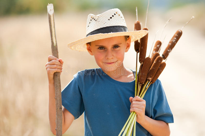 Kid with straw hat playing stock photos