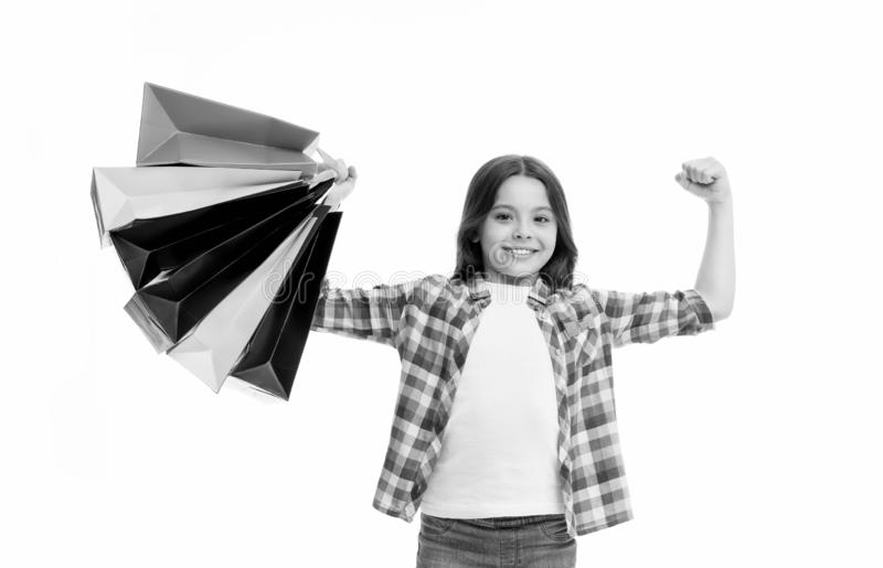 Kid strong makes independent purchases. Girl carries shopping bags isolated on white background. Girl fond of shopping. Child cute shopaholic with bunch stock photography