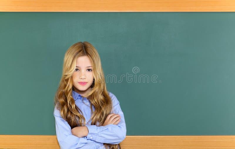 Kid student girl on green school blackboard. Kid student girl on green blackboard posing with smile royalty free stock photography
