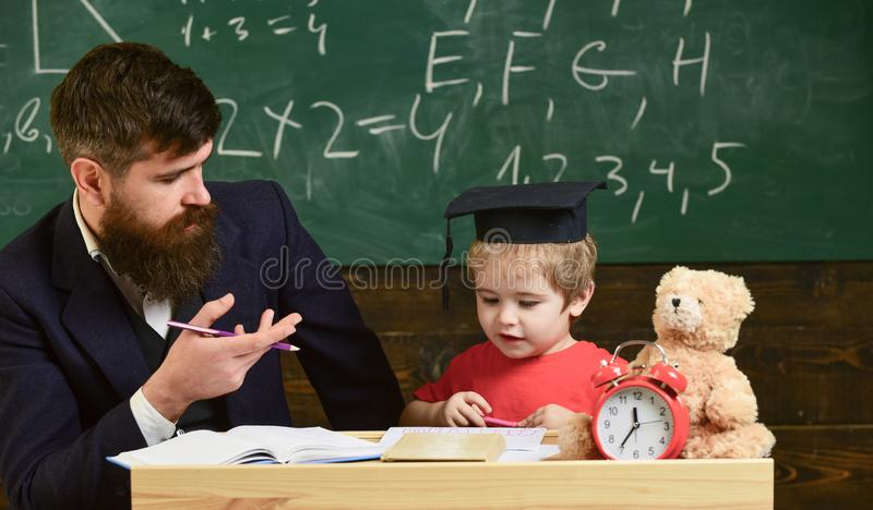 Kid studying with teacher. Father teaches son, discuss, explain. Education concept. Elementary education. Teacher in royalty free stock photo