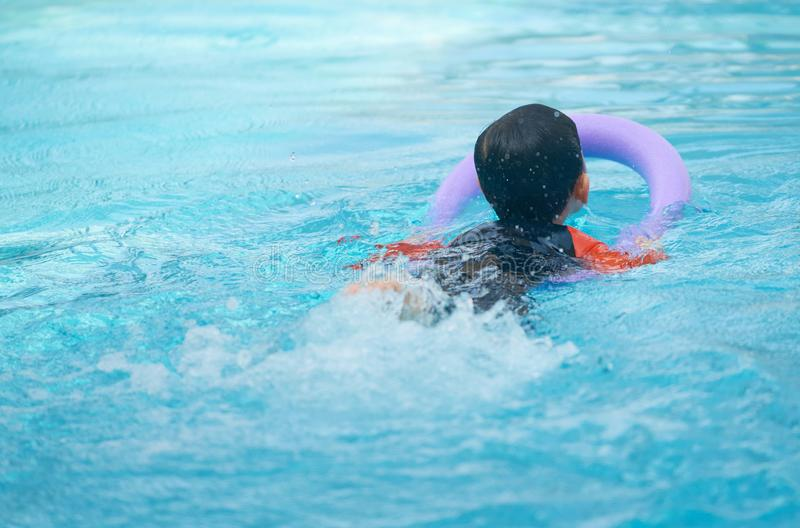 Kid swim with foam noodle for learning swimming class in water p. Ool,back view royalty free stock photo