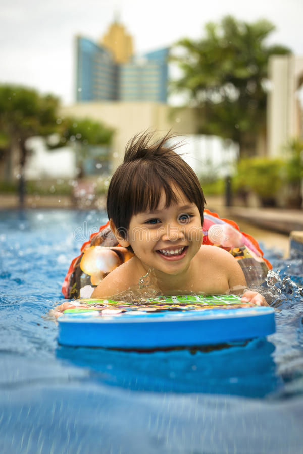 Young mixed happy smiling Asian boy kid swimming in the hotels pool stock image