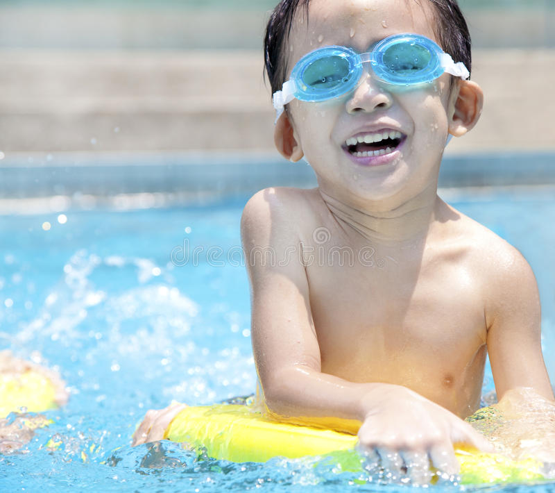 Kid in Swimming Pool. Happy asian kid in Swimming Pool royalty free stock image
