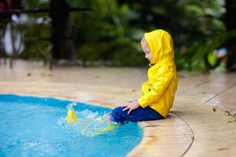 Kid in swimming pool in rain. Tropical storm royalty free stock photos
