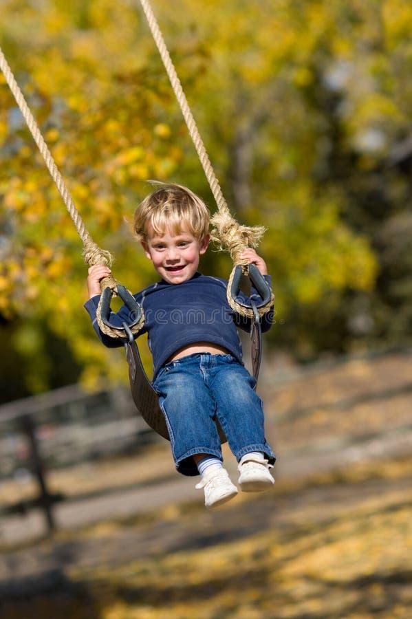 Kid on swing royalty free stock photo
