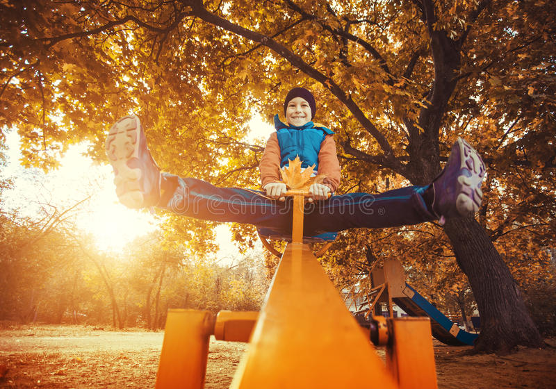 Kid swinging at the park in autumn royalty free stock photos