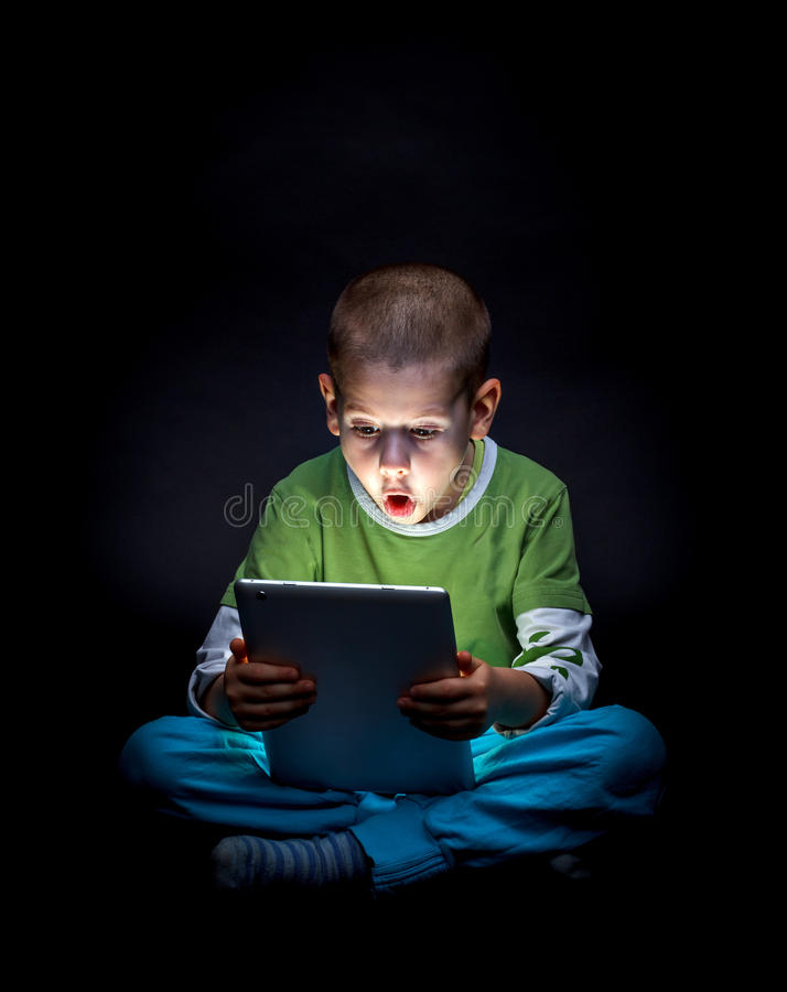 Kid with tablet. Surprised kid with tablet computer stock photography