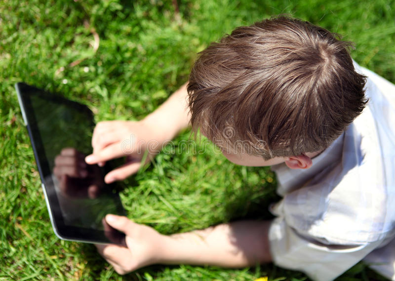 Kid with Tablet Computer. On the Summer Meadow stock images