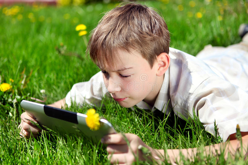 Kid with Tablet Computer. On the Summer Meadow royalty free stock image