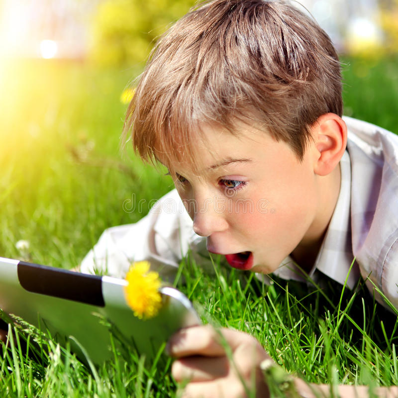 Kid with Tablet Computer. Surprised Kid with Tablet Computer on the Summer Meadow royalty free stock photo