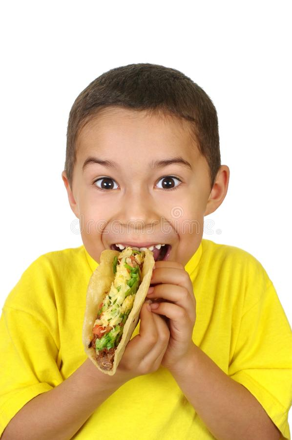 Kid with a taco. Hispanic boy holding a Mexican-style taco, isolated on white background stock photo