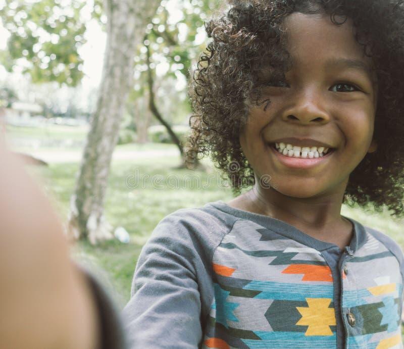 Kid taking selfie in park.  stock image