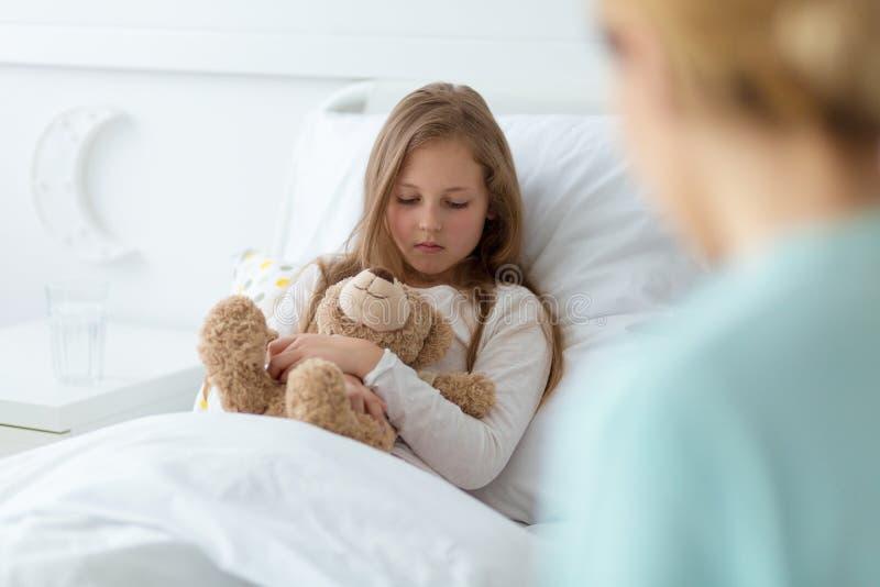 Kid with a teddy bear afraid of a diagnosis stock photos