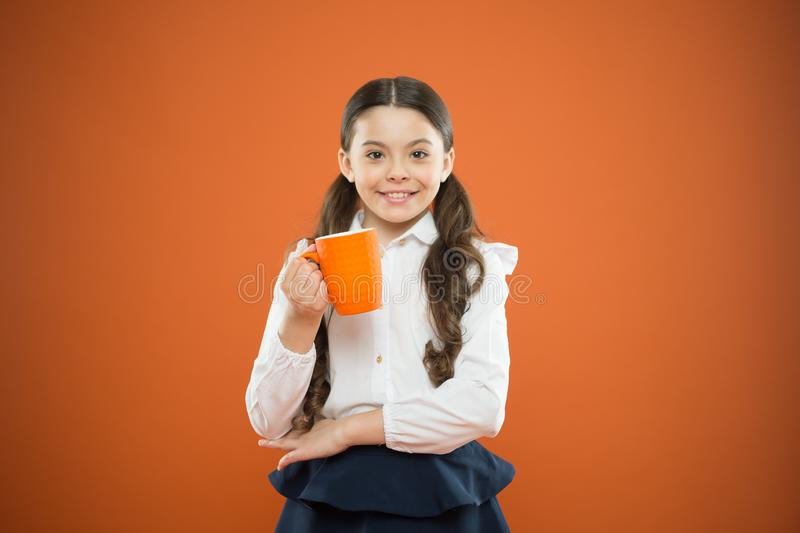 Kid tested breakfast. Little child having tea or milk for breakfast on orange background. Happy cute pupil holding book stock photos