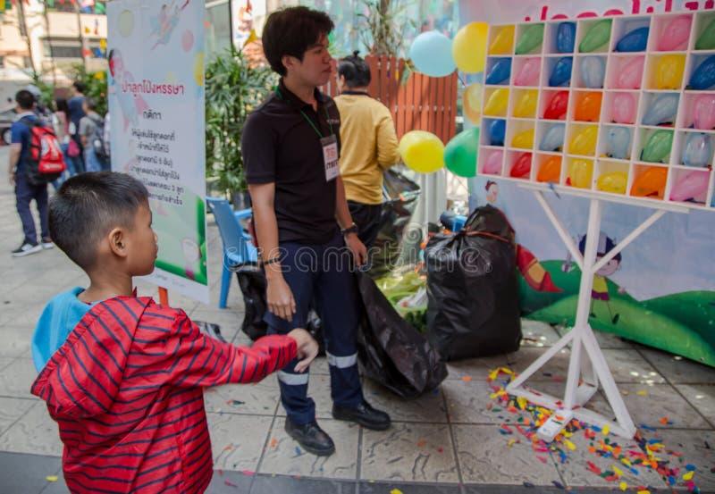 Kid throw dart at balloons. Bangkok, Thailand - January 13, 2018: Asian boy throwing dart at colorful balloon in Children Day 2018 royalty free stock photos