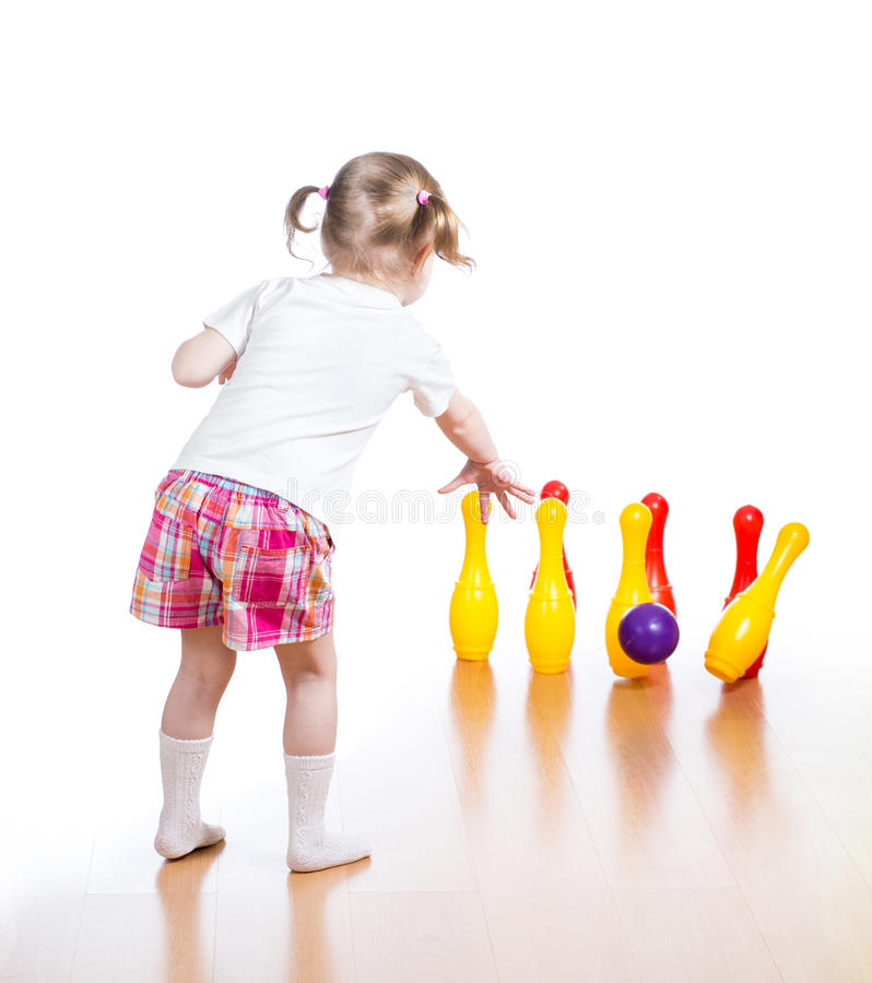 Kid throwing ball to knock down toy pins stock image