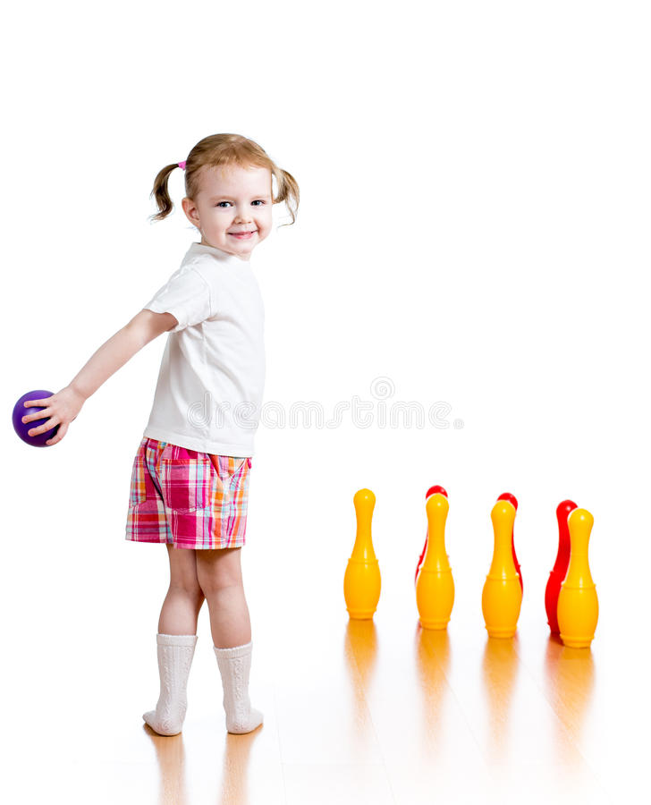 Kid throwing ball to knock down toy pins. Kid throwing ball to knock down toy bowling pins. Focus on child girl standing back royalty free stock images