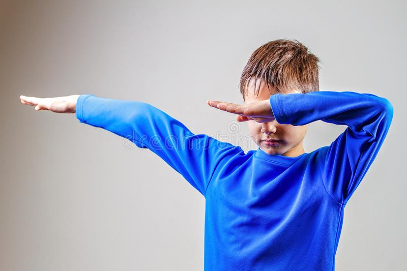 Kid throws dab on the background of a gray wall.  royalty free stock image