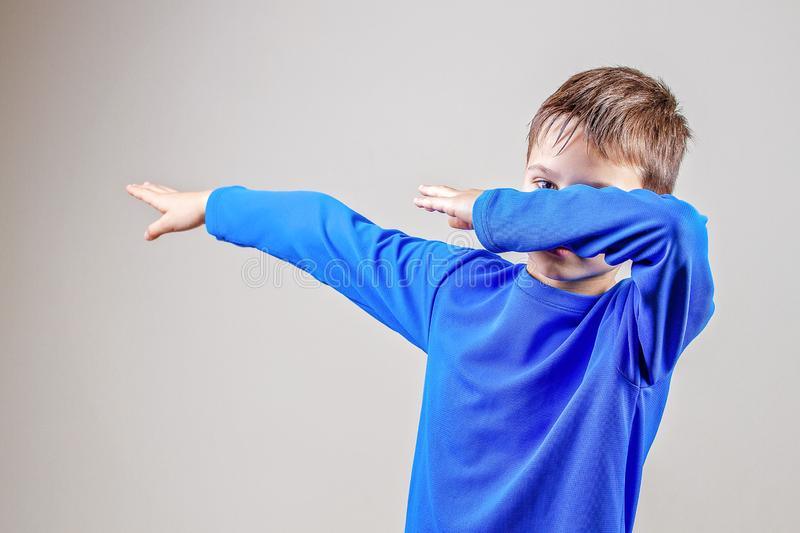 Kid throws dab on the background of a gray wall.  stock photos