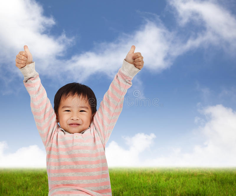 Kid with thumbs up. Smiling kid with thumbs up and standing on the green meadow stock photo