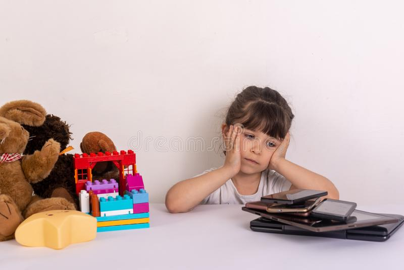 Kid tired because of too much information. Stressed little girl sitting near phones, smartphones, laptops, pc tablets. royalty free stock photography