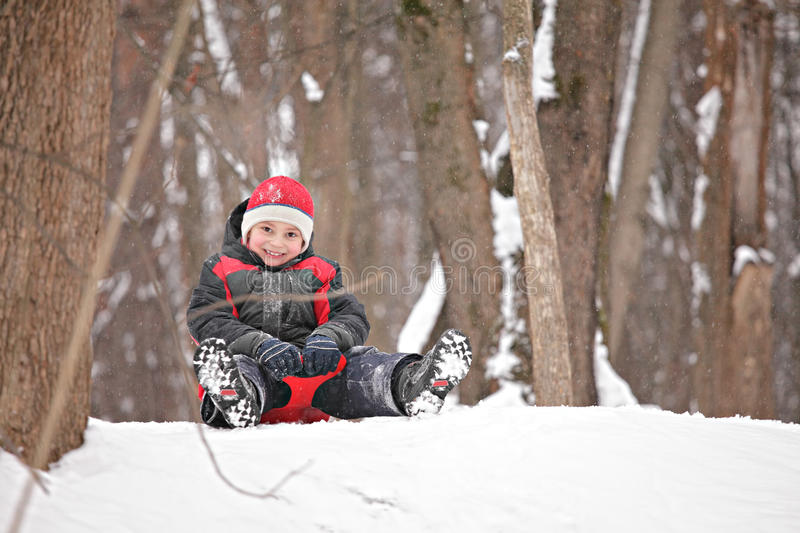 Kid On Tobbogan On Top Of Hill Royalty Free Stock Photos