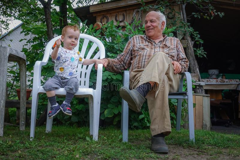 Kid toddler and his grandfather stock image