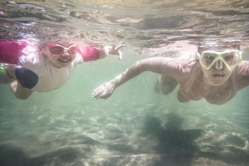 Child toddler learning swimming underwater with mother during summer beach holidays vacation stock image