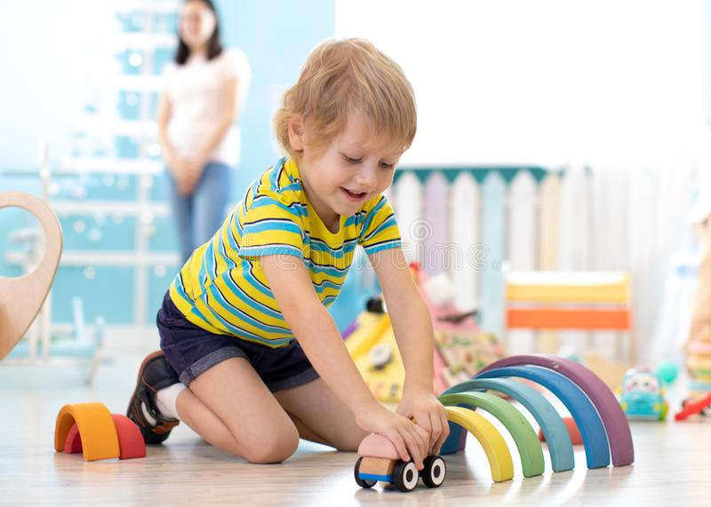 Kid toddler playing wooden toys in kindergarten or nursery stock photos