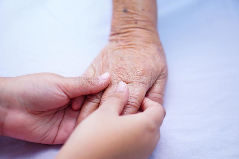 Kid touching hands Asian senior or elderly old lady woman patient with love, care, helping, encourage and empathy. Kid touching hands Asian senior or elderly stock photos