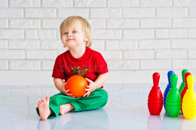 Kid and toy bowling. Baby boy playing with colorful plastic toy bowling stock photos