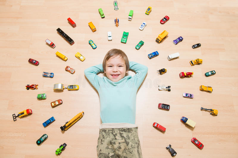 Kid with toy cars around him. Adorable young boy lying on the ground with toy cars around royalty free stock images