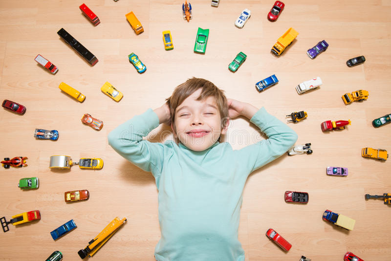 Kid with toy cars around him. Adorable young boy lying on the ground and dreaming with toy cars around stock photography