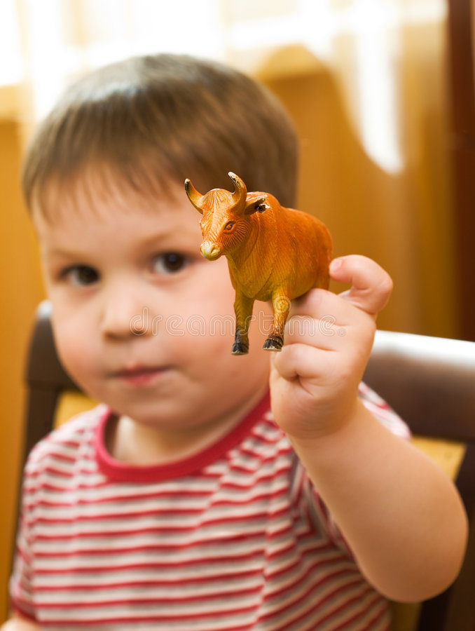 Kid with a toy cow stock photos